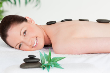 Smiling young woman with massage stones on her back