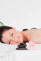 Portrait of a red-haired woman receiving a hot stone massage