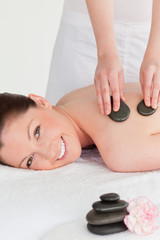 Smiling young redhead woman having a hot stone massage