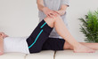 Masseuse massing the knee of an athletic woman