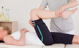 Fototapety Masseuse stretching the right leg of an athletic woman