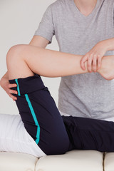 Portrait of a masseuse stretching the right leg of an athletic w