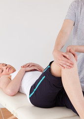 Portrait of a masseuse massing the knee of a young woman