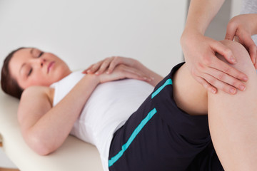 Masseuse massing the knee of a young woman