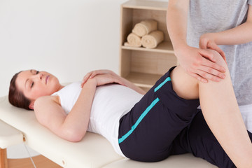 Masseuse massing the knee of a cute woman
