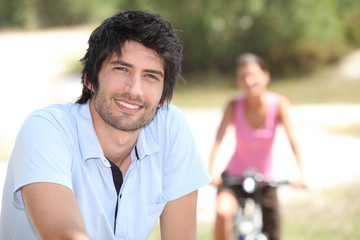 man and woman riding bike outdoors