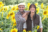 a couple of farmers in a sunflowers field