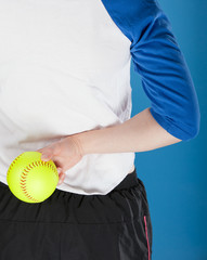 A woman holding a softball behind her back