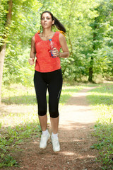 Fitness girl jogging through the woods