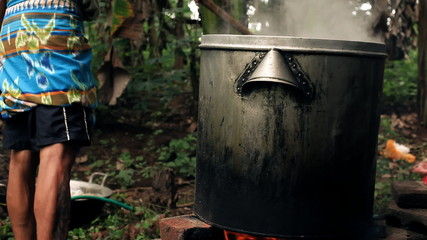 Man preparing food in a big steel pot