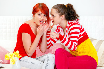 Girl whispering gossips her girlfriend and pointing in corner.