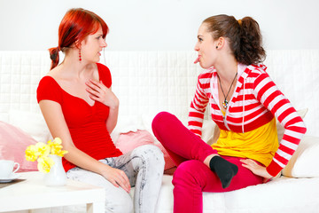 Funny girl sitting on sofa and showing  tongue her girlfriend.