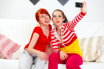 Funny girls showing tongues while photographing themselves.