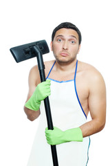 Sad young man in apron holding vacuum cleaner brush