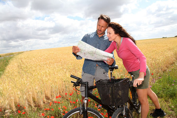 Couple riding looking at map on bike ride