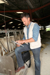 Breeder in barn with electronic tablet