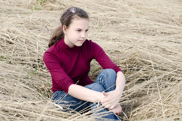 Girl Sits on a dry grass