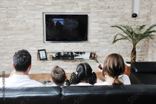 family wathching flat tv at modern home indoor - 33100102