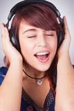 Teen woman listening music at headphones