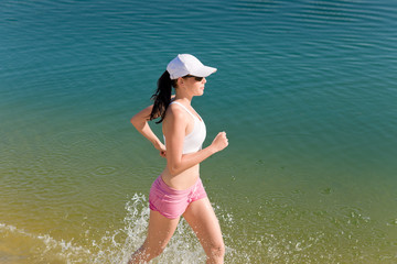 Summer sport fit woman jogging along seashore