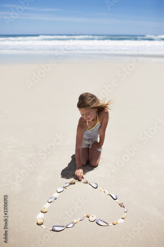 Girl making heart-shape with shells on beach