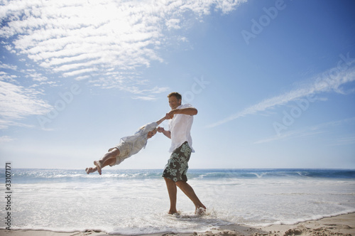 Father spinning daughter on beach