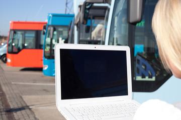 junge blonde frau mit laptop vor bussen