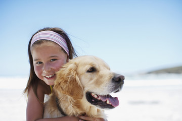 Girl hugging dog on beach