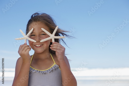 Girl holding starfish on beach