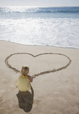 Girl drawing heart in sand on beach