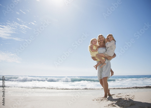 Mother holding daughters on beach