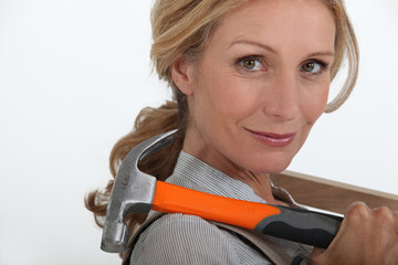 Blond woman holding hammer over shoulder