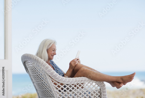 Senior woman using digital tablet in chair