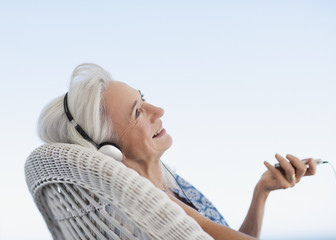 Senior woman listening to music on mp3 player