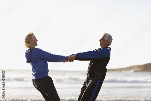Senior couple holding hands on beach