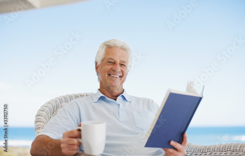 Senior man with coffee and book on beach patio