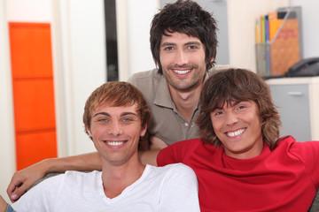 Three smiling lads sitting on a sofa