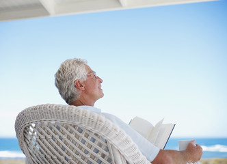 Senior man reading book on beach patio