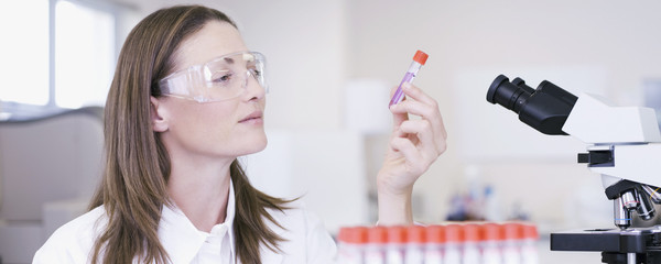 Scientist examining vial in laboratory