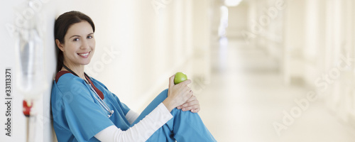Nurse sitting with apple in hospital corridor