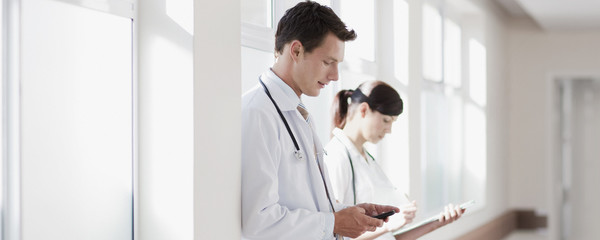 Doctors with clipboard and cell phone in hospital corridor