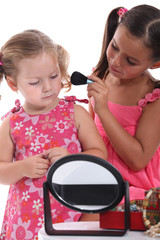 Two little girls playing with make-up