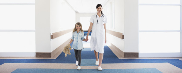 Nurse and girl patient in hospital corridor