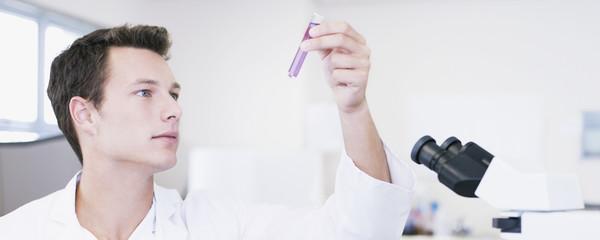 Scientist examining vial in laboratory
