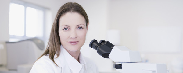 Scientist with microscope in laboratory