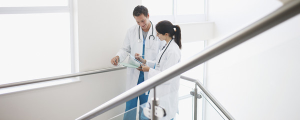 Doctors looking at medical chart on stairs