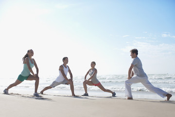 Friends stretching on beach