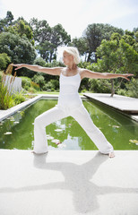 Woman doing yoga by pond