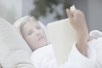 Woman reading book in lounge chair