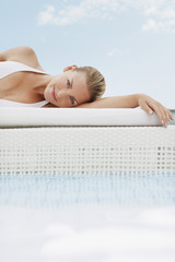 Woman laying on cushion at poolside